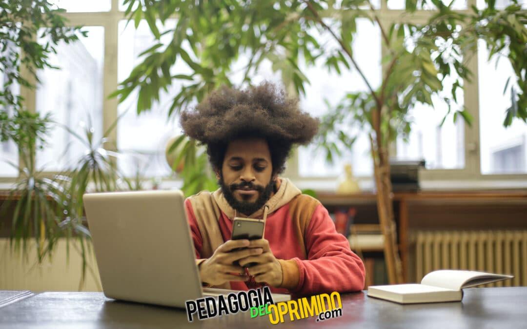 Estudiante mirando el móvil con las 5 app para ser mas productivo mientras esta trabajando en su portátil